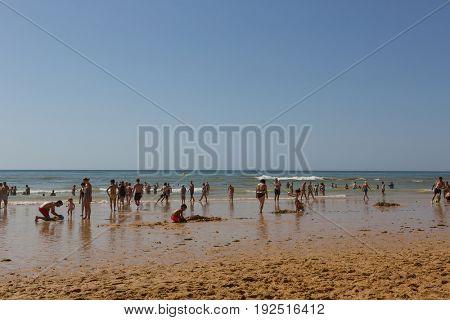 ALBUFEIRA, PORTUGAL - AUGUST 23, 2016: People at the famous beach of Olhos de Agua in Albufeira. This beach is a part of famous tourist region of Algarve.
