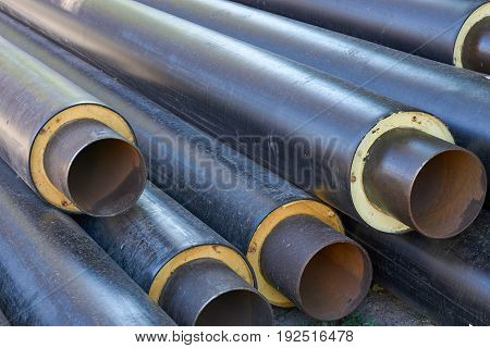 stack of big metal pipes tubes with heater isolation insulation and pvc shell at construction site