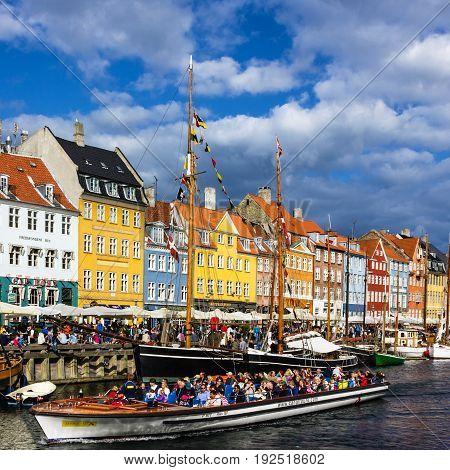 COPENHAGEN, DENMARK - MAY 7, 2017: Seafront Nyhavn and tourist boat in the center of Copenhagen, Denmark