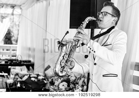 Saxophonist In White Jacket Playing The Saxophone. Saxophonist Jazz Man With Saxophone On Wedding Pa