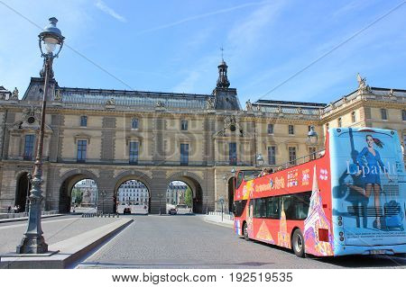 PARIS, FRANCE - JUNE 5, 2017: Hop on Hop off red tourist tour bus in front of Louvre museum. The bus helps tourists to visit all popular travel landmark and attractions in the city of Paris, most visited city in Europe.