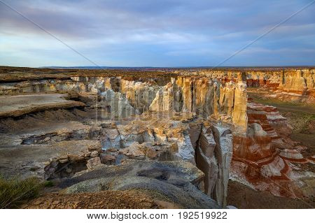View of Coalmine Canyon near Tuba City Arizona. A dramatic canyon late in the day with sunlit waning and highlighting the hoodoos. This shows the different textures and rock formations of the canyon.