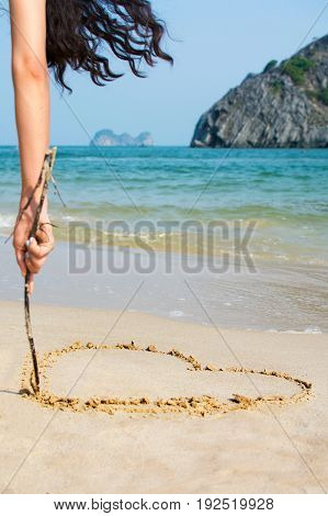 Girl Drawing A Hearth Shape On The Beach