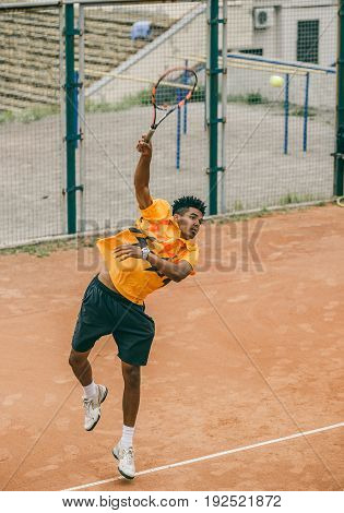 A young man beats off a ball with a tennis racket. A tennis player holds a duel on a tennis court.