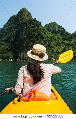 Girl Kayaking On Seaside Of Halong Bay In Vietnam