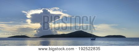 Majestic panoramic seascape with clouds in form of holy resurrection over Luis Pena Cay and calm sea with sailboat on Caribbean Island of Isla Culebra in Puerto Rico