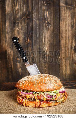 Tasty big hamburger served with knife on paper. Horizontal studio shot.