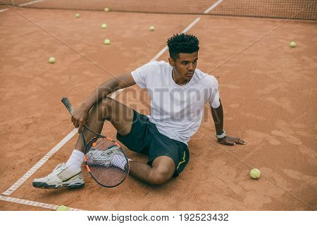 Tennis player is having a quick time break. African man sits on the ground of a tennis court.