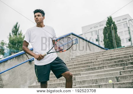 Handsome young man in polo shirt holding tennis racket and looking concentrated while standing on concrete steps.