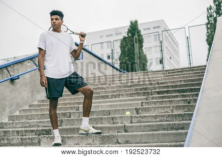 Side view of serious young man in polo shirt carrying tennis racket on shoulder and looking away while standing on concrete steps.