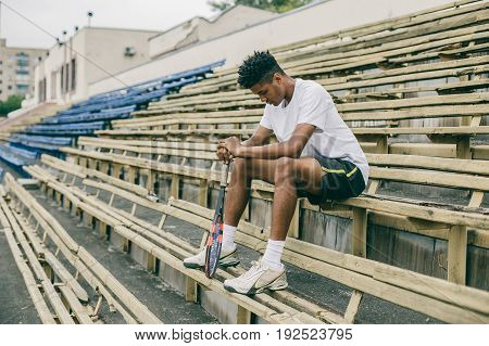 Professional tennis player resting from tennis match. African man sitting on a bench holding his head down.
