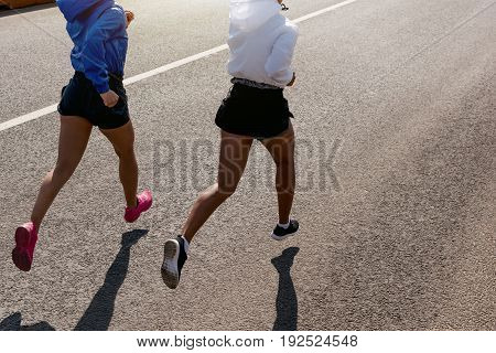Back view of two unrecognizable women running on road