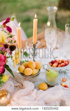 picnic, dating, wedding, valentines day, weekends concept - romantic table setting for newlyweds with flowers, burning candles, crystal glasses and such treat like apricots, pears and cherries