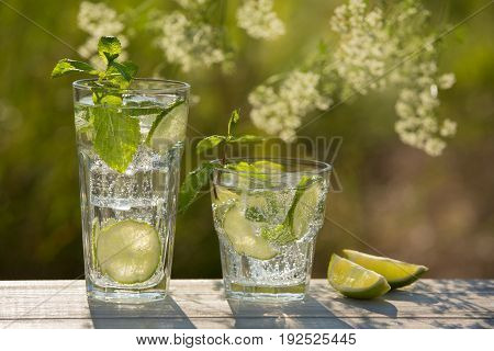 two glasses of soda water on an old board on nature ice bubbles grapefruit spike