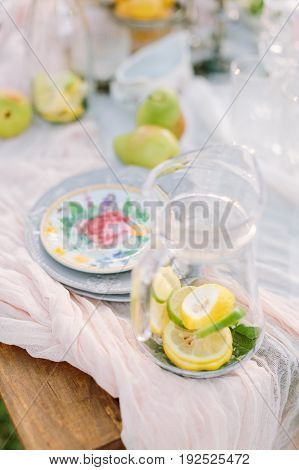 lifestyle, decoration, healthlife, country concept - still-life with jug full of sliced lemon and mint and plates with flower print on light pink draping