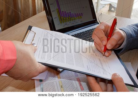 Signature of Documents in the Office. Businessman Sitting at desk sign Documents. Document on the table Document Signing People Work. Colleagues working together in office