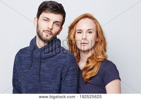 Portrait of two young beautiful Caucasian people wearing blue clothes posing indoors on white background. Beautiful girl with long red hair looking confident while standing behind her handsome bearded man. Love and trust concept.