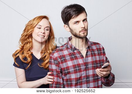 People and technology. Happy couple using mobile phone together. Pretty girl with ginger hair and cute smile looking at screen of her bearded serious friend's electronic device. Human emotions and expressions.