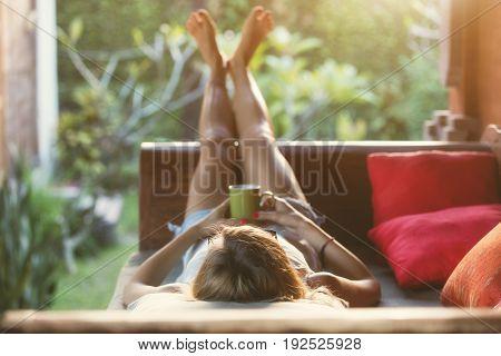 Girl drinking coffee / tea and enjoying the sunrise / sunset in garden. Shallow focus on the head / hair.