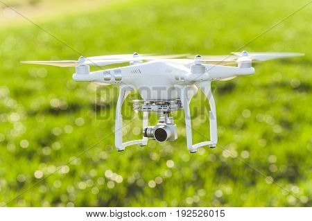 RUSSIA, ROSTOV-ON-DON - APRIL 20, 2017: quadrocopter on takeoff, low flying white drone with build-in camera at background of summer grass field, closeup front view