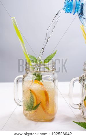 Water Pouring Into Jar With Orange And Mint
