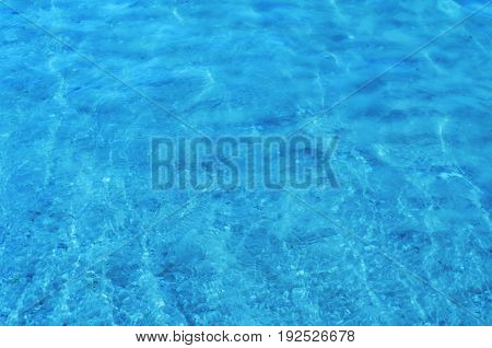 Crystal clear sea water ripples sparkling in the noon sun. Rippled water with bottom sand and shells seen underwater