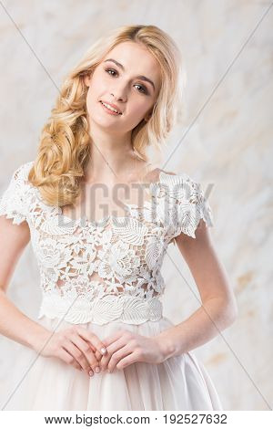 fashionable wedding dress, beautiful blonde model, bride hairstyle and makeup concept - young smiling woman in white gown indoors on light background, luxury female posing in the studio