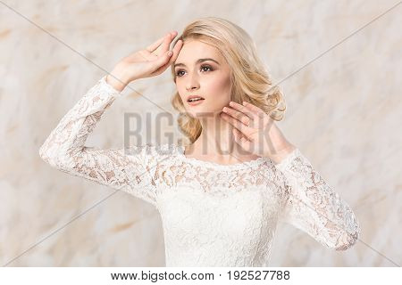 fashionable white gown, beautiful blonde model, bride hairstyle and makeup concept - closeup young lady in wedding festive dress standing indoors on light background, pretty woman romantic posing