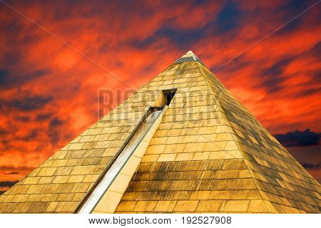 Stone high pyramid with a waterfall, against a bright colorful sunset