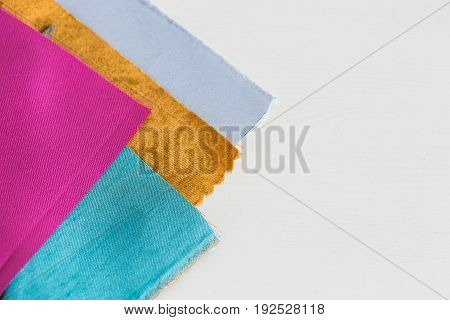 sewing, tailoring and fashion concept - beautiful colored patchwork fabric, flaps ready for stitching over white background, macro on tools at workshop, empty space for the text