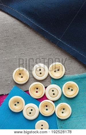 sewing, patchwork, tailoring and fashion concept - close-up on a scattering of white buttons for clothing, macro over background of blue, gray, purple flaps of textile fabric, flat lay, top view