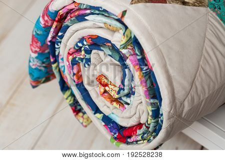patchwork, sewing and fashion concept - close-up on cute colorful quilted blanket at white shelves with storage compartment in studio, white floor in a warehouse of finished products, side view