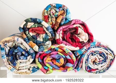patchwork, sewing and fashion concept - bright beautiful quilts stacked in several rows in height for the storage, sale of finished stitched coverlets on white background, front view