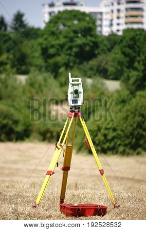 A leveling device on a three-armed tripod for landscape surveying.