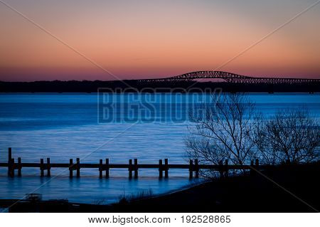 Early morning just before sunrise silhouette of a dock and bridge in Virginia
