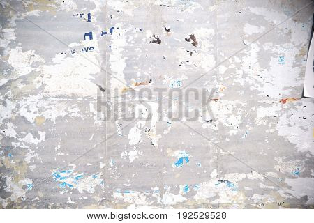 The close-up of a billboard with torn paper shreds of posters and advertising posters.