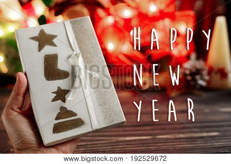 Happy New Year Text Sign On  Hand Holding Christmas Wrapped Present Box On Background Of Warm Garlan