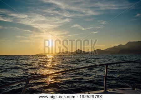 Coast of Montenegro at sunset, view from the sea, silhouettes of mountains