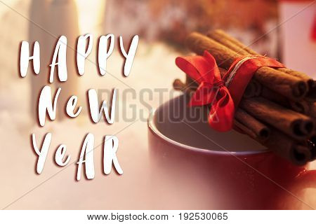 Happy New Year Text Sign On Cinnamon Sticks With Ribbon On Red Cup. Winter Cozy Moment. Space For Te