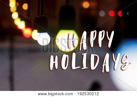 Happy Holidays Text Sign On Colorful Retro Garland Lights Bulbs At Street In European City At Winter