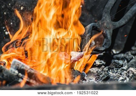 tongs holding a metal workpiece in hot coals