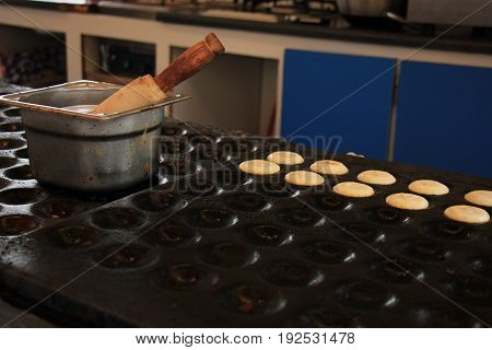 Poffertjes Dutch small fluffy pancakes made on hot cast iron plate served with powdered sugar and butter.
