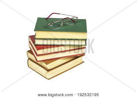 На светлом фоне лежит стопка книг в жестком переплете и очки для чтения