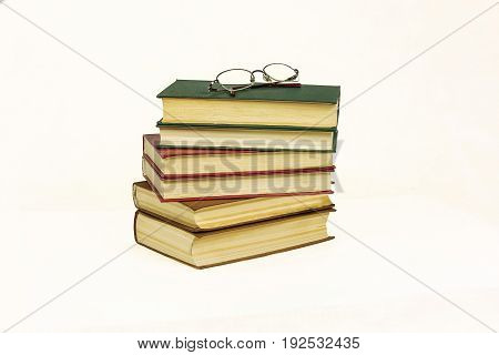 On the white surface is a pile of hard-bound books and reading glasses