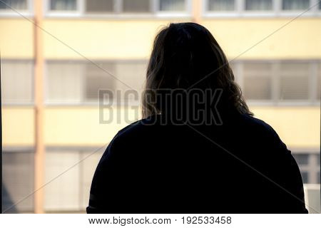 Back View Of Silhouette Of A Woman Putting On Makeup In Front Of A Window