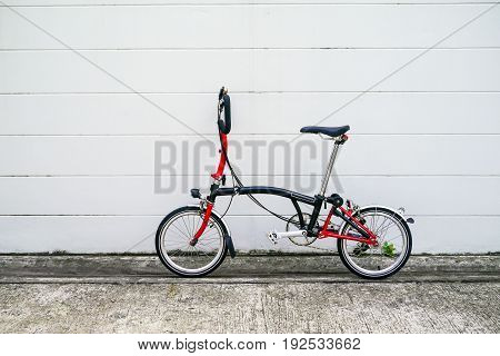 Black and red folding bicycle in front of white concrete wall