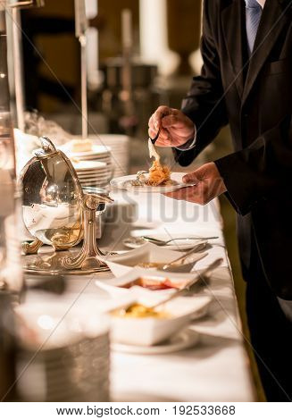 Businessman hands taking food in buffet line indoor in luxury hotel
