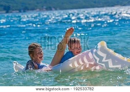 Happy Sister & Brother Children Playing with Inflatable Mattress at Blue Sea
