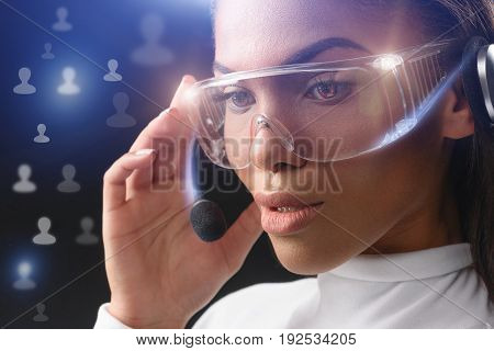 Thoughtful young african woman is speaking by headset. She is touching futuristic eyeglasses and microphone. Social network communication concept