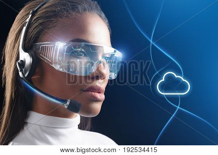 Lets speak. Pensive young african woman is communicating through future network device. She is wearing special glasses and sees online cloud